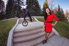 Woman and BMX cyclist doing a stunt jump Royalty Free Stock Photography