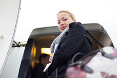 Woman boarding airplain. Casually dressed young stylish female traveller boarding airplane in cold winter weather wearing winter coat and wool scarf. Woman on Stock Images