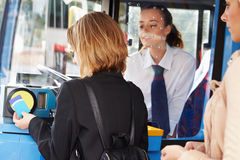 Woman Boarding Bus And Using Pass. On Machine With Bus Driver Looking Over Stock Images