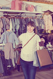 Woman boast new acquiring. Smiling pregnant woman boast new acquiring in the children`s clothes  shop Stock Photo