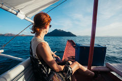 Woman on boat approaching tropical island Stock Photo