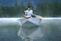 Woman on boat in fog. Woman on a boat in the fog or steam on a lake stock photography