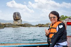 Woman on the boat at Ko Hin Sorn island in Thailand. Woman tourist in life vest wearing sunglasses on the boat thumb up for the beautiful of the sea and nature royalty free stock images