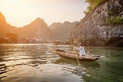 Woman in boat returns to fishing village, Ha Long Bay, Vietnam Stock Photography