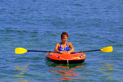 Woman row boat. Vacationer woman rowing inflatable boat in calm  sea on hot nice summer day.Picture taken on August 10th,2014 Royalty Free Stock Photos