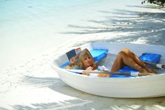 Woman in boat under palm Royalty Free Stock Images