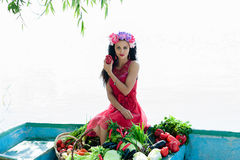 Woman on the boat with vegetables holding pepper Stock Photo