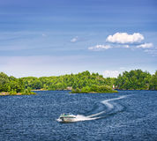 Woman boating on lake. Woman piloting motorboat on lake in Georgian Bay, Ontario, Canada Royalty Free Stock Photos