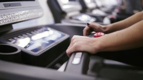 Woman bodbuilder setting up a program and timer on treadmill set at the gym preparing to start jogging.  stock footage