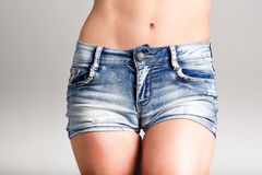 Woman body in denim jeans shorts on white background Stock Images