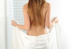 Woman body entering in the shower. Back view of a woman body entering in the shower with a white towel Stock Image