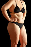 Woman body fat black background. Body of a middle aged woman in bikini with excessive fat on waist and thighs, dimpled skin, black background Stock Photos