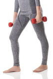 A woman body, hands, legs in gray sports thermal underwear doing exercises using red dumbbells. Royalty Free Stock Photo