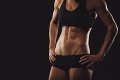Woman body with muscular abs. Slim and fit woman belly with hands on hips. Mid section of young tanned woman body with muscular abs on black background with stock images