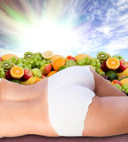 Woman body  over fresh fruits and sunny sky Royalty Free Stock Photo