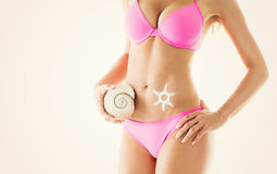 Woman body. Perfect Woman body in a bikini with sun-shaped sun cream and shell. Close-up Stock Images