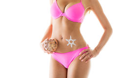 Woman body. Perfect Woman body in a bikini with sun-shaped sun cream and shell. Close-up. Isolated on white background Royalty Free Stock Photography