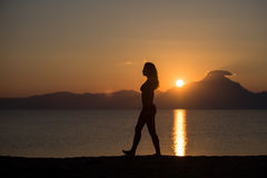 Woman body silhouette at sunrise at the beach. Woman walking on the beach at sunrise in Sithonia, Greece Royalty Free Stock Photos