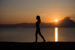 Woman body silhouette at sunrise at the beach. Woman walking on the beach at sunrise in Sithonia, Greece Royalty Free Stock Image