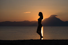 Woman body silhouette at sunrise at the beach. Woman walking on the beach at sunrise in Sithonia, Greece Stock Image