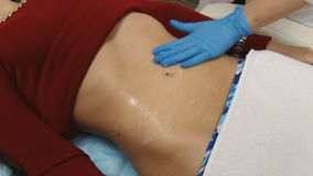 Woman body treatment at medical spa center. applying moisturizer on stomach stock footage