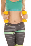 Woman body yellow weights stripe pants. A close up of a woman's body working out with weights Royalty Free Stock Image