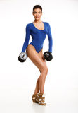 Woman bodybuilder in blue body, posing in the studio with dumbbe Stock Photo