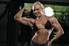 Woman Bodybuilder Flexing Muscles. Serious Woman Bodybuilder Standing In The Gym And Flexing Muscles Royalty Free Stock Photo
