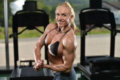 Woman Bodybuilder Flexing Muscles. Serious Woman Bodybuilder Standing In The Gym And Flexing Muscles Stock Image