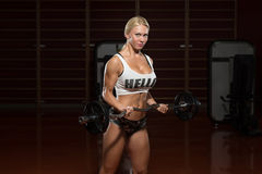 Woman Bodybuilder Performing Biceps Curls With A Barbell. Young Woman Athlete Doing Heavy Weight Exercise For Biceps Stock Photo