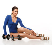 Woman bodybuilder posing after a workout near dumbbells Royalty Free Stock Photos