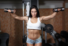 Woman bodybuilder training with dumbbell. Stock Photos