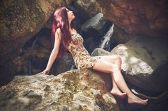 Woman in Bodycon Mini Dress Sitting on Boulder Royalty Free Stock Images