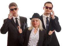 Woman with bodyguards. A women with two bodyguards behind her Stock Photos