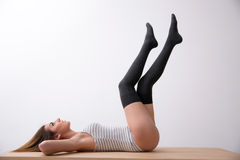 Woman in bodysuit lying on the table Royalty Free Stock Photography