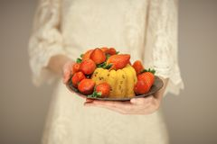 Woman, boho bride holding little cake on a plate with strawberries stock photo