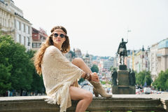 Woman in boho chic clothes relaxing on stone parapet in Prague Stock Image