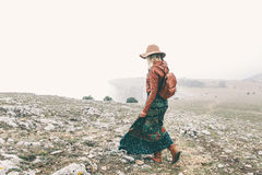 Woman in boho clothing traveling in fog weather Royalty Free Stock Photo