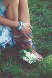 Woman boho fashion style details on hands and barefoot. Woman summer boho fashion style details on hands and barefoot bracelets, anklets and rings outdoor day in Stock Photos