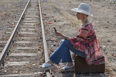 Woman boho sitting on a suitcase. Boho style woman in hat sitting on an old vintage suitcase next to a railway track and holding a mobile phone. Profile view Royalty Free Stock Images
