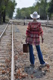 Woman boho standing with suitcase. Boho style woman in hat standing next to a railway track, holding an old vintage suitcase. Rear view Royalty Free Stock Image