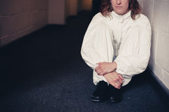 Woman in boiler suit sitting in corridor Stock Image