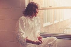 Woman in boiler suit by window Royalty Free Stock Images