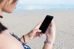 Woman& bonito x27; mão de s usando o telefone esperto na praia Foto de Stock