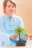 Woman with bonsai tree Stock Photos