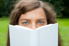 Woman with book. Portrait of a young woman reading in a white book stock images