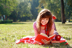 Woman with book. The happy woman lays on a grass and reads the book Stock Photo