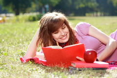 Woman with book. The happy woman lays on a grass and reads the book Royalty Free Stock Images