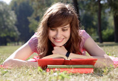 Woman with book. The happy woman lays on a grass and reads the book Stock Photography