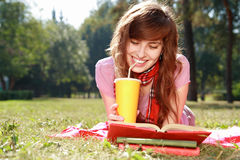 Woman with book. Woman lays on a grass, reads the book and drinks from a paper cap Royalty Free Stock Photo